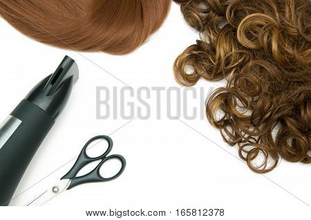 Curly brown hair and red straight hair with hair dryer and scissors isolated on white