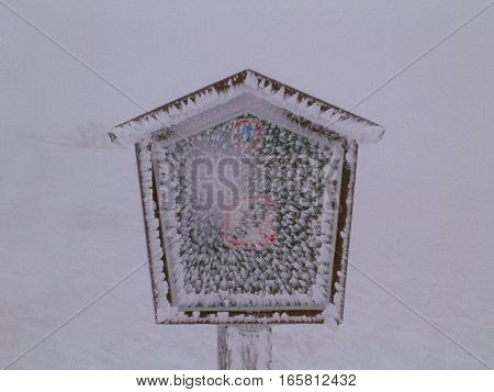 Photo of an ice-covered sign surrounded by snow