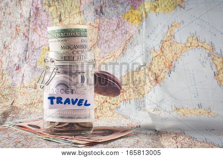 jar with money on used map. holiday savings