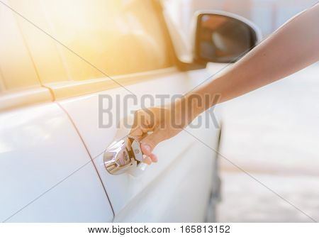 Close up woman hand opening white car door.