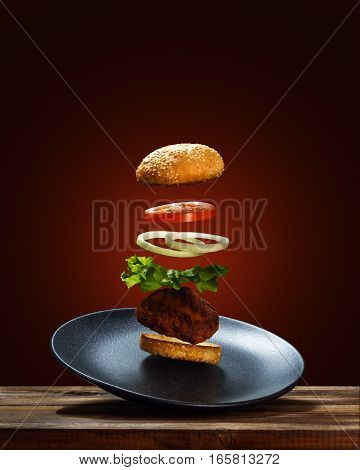 Flying Ingredients Burger On A Black Ceramic Plate Isolated On A Red Background.