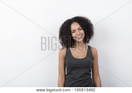 Young cheerful brunette with toothy smile indoors