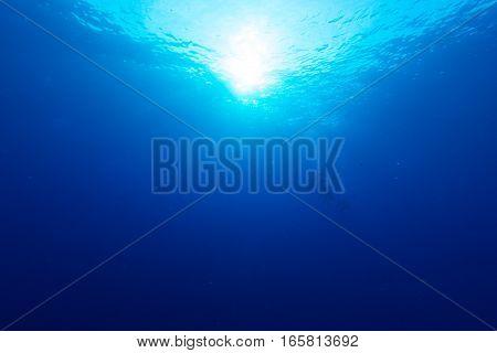 Rays of sunlight shining into sea, underwater view in Miyakojima Island.