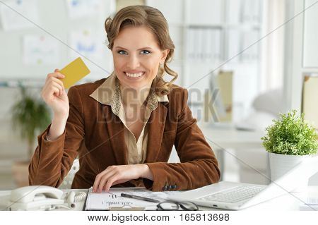 Portrait of young businesswoman holding credit card