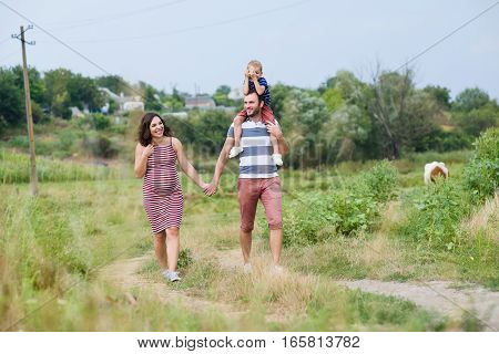 Happy pregnant family having fun in summer nature. A child on the shoulders of dad. Countryside walk along rural road.