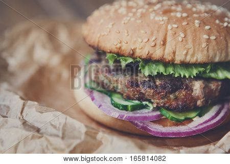 Classic american fast food background. Burger whole grain bun with grilled on barbecue meat and onions on wood in craft paper, closeup. Hamburger with fresh vegetables composition. Filtered