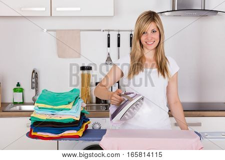 Smiling Young Woman Ironing Clothes With Electric Iron At Home