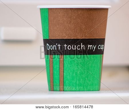 paper coffee cup with the inscription standing on the windowsill