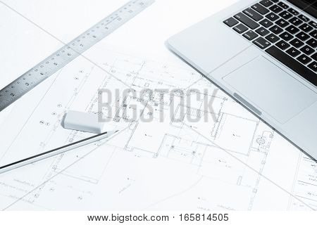 Pen, Metal Ruler, Rubber And Notebook Over House Construction Blueprint With Blue Tone Effect