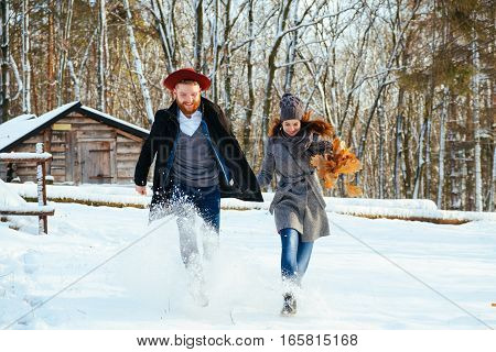A loving happy young couple emotionally runs in the winter woods. View back