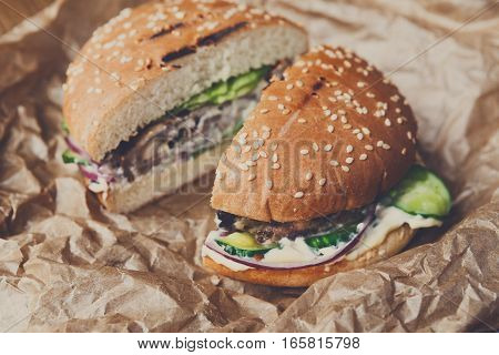 Classic american fast food background. Cut in half burgers with grilled meat and onions on wood. Hamburgers with fresh vegetables on craft wrapping paper. Selective focus, shallow DOF