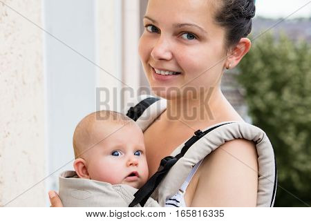 Portrait Of A Smiling Mother Carrying Her Baby In A Baby Carrier