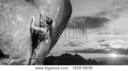 Young attractive female rock climber climbing challenging route on steep rock wall against scenic sunset background. Summer time. Climbing equipment. Black and white