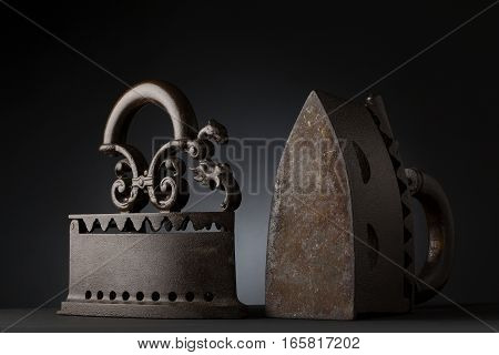 two vintage rustic iron on a table