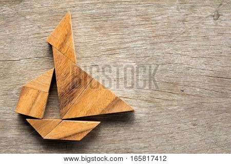 Chinese tangram puzzle in sail boat shape on wooden background