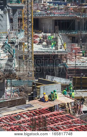 Laborers having a short break during work on modern construction site works in Dubai. Fast urban development concept.
