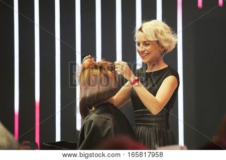 Model receives finishing touches to her hair at a stage.