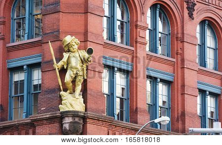 New York, USA, november 2016: a golden puck statuette by Henry Baerer decorating the puck building on lower manhattan