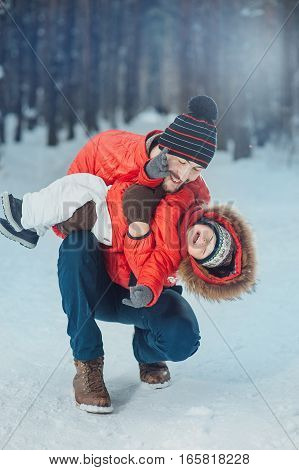 father holding the baby in his arms on the winter background