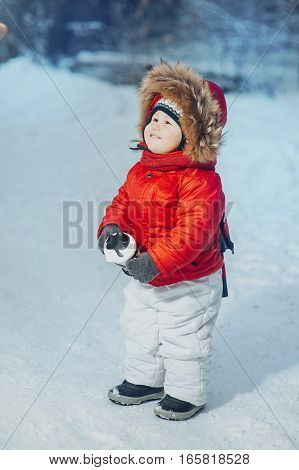 child smiling on the background of the winter forest