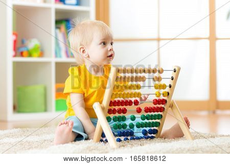 Preschooler baby learns to count. Cute child playing with abacus toy. Little boy having fun indoors at home, kindergarten or day care centre. Educational concept for preschool kids.