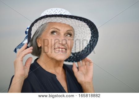 Portrait of a beautiful mature woman posing in hat