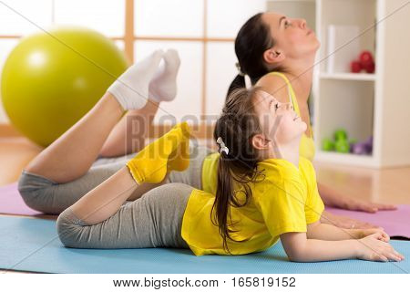 Mom and child daughter do gymnastics. Family sports