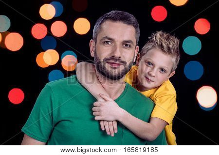 Portrait of smiling father and son looking at camera