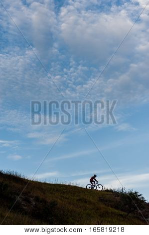 Silhouette Of A Cross Country Cyclist Going Downhill