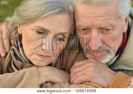 Portrait of a sad senior couple in autumn park