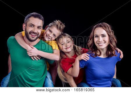 Happy family in colorful t-shirts hugging and smiling at camera on black