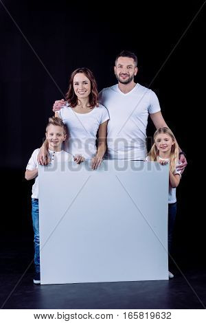 Smiling family in white t-shirts holding blank white card and looking at camera