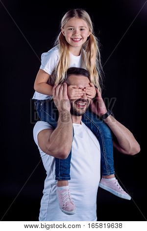 Happy father and daughter in white t-shirts having fun together on black