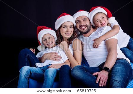 Happy family sitting in Santa hats and looking at camera on black