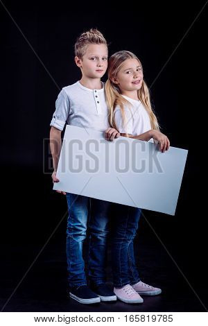 Smiling siblings standing with blank white card and looking at camera on black