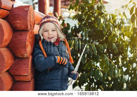 Little boy walking outdoor in the winter time and playing with icicle.