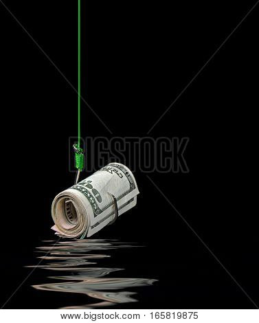 roll of American money on fish hook with water reflection on black
