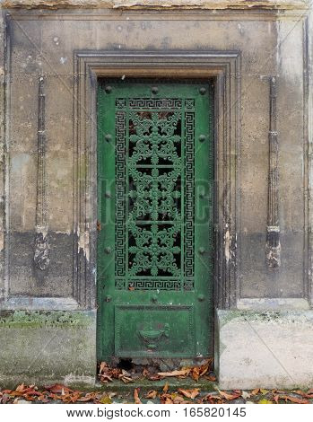 A weathered and antique green closed iron or steel door of an old tomb / crypt, decorated with ornaments of flowers, geometric shapes and a border line frames.