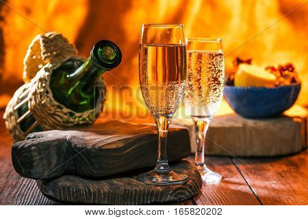 Sparkling wine in glass andbottle. Fruit on the background. Fireplace lighting