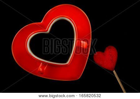 Red cup of coffee in the shape of a heart for lovers on a black background. Valentine Day concept.