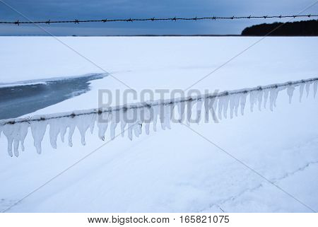 Snowy open winter landscape with icy barb wire fence