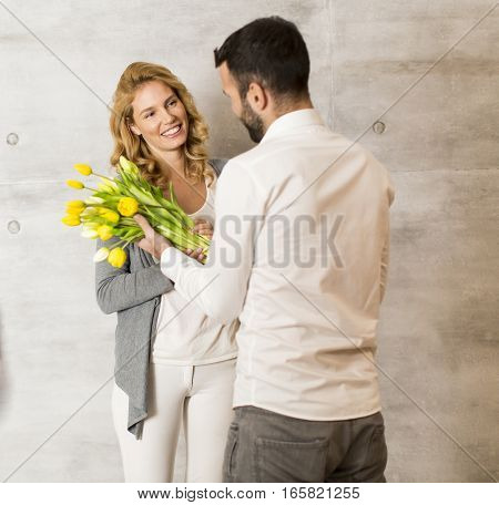 Young Man Giving To Girl A Bouquet Of Tulips