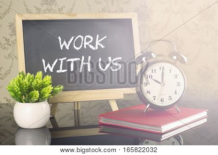 Work With Us on blackboard with clock and flare