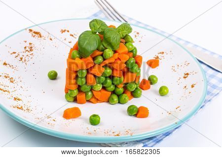 Mix orange carrots and green peas with olive oil and curry. Studio Photo