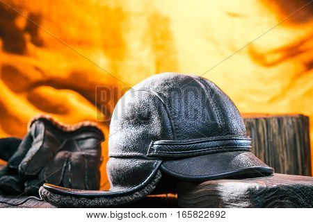 Male winter accessories: hat and gloves of dark sheep-skin. Natural wood. Fire lighting