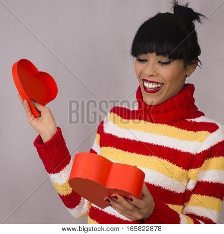 Surprised happy woman is opening gift box of heart shape.