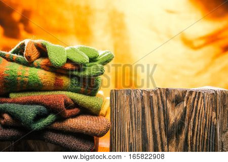 Knitwear stack near wood stand over fire background