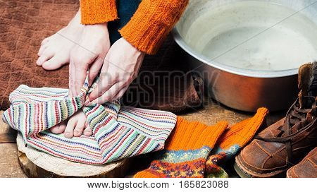 Bare feet on the towel and hands drying them near basin with warm water, boots and wool socks after footbath