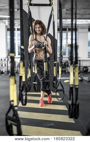 Happy sportive woman with curly hair stands in the gym on the background of the partition. She wears dark sportswear with red sneakers. She looks into the camera with a smile and holds TRX straps.