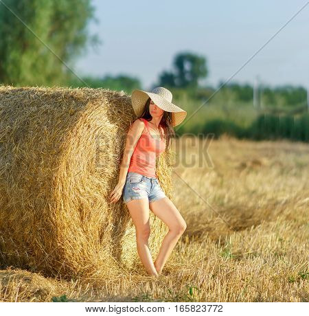 The girl in the shorts and hat stands near a stack of straw